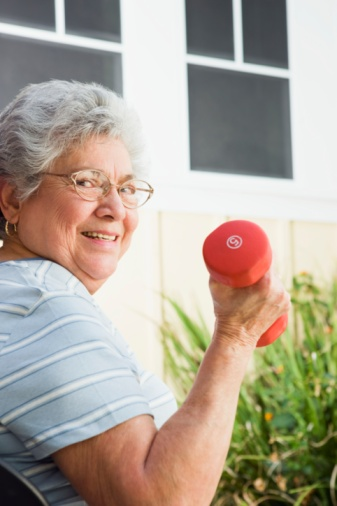 Senior woman lifting weights --- Image by  © Steve Hix/Somos Images/Corbis
